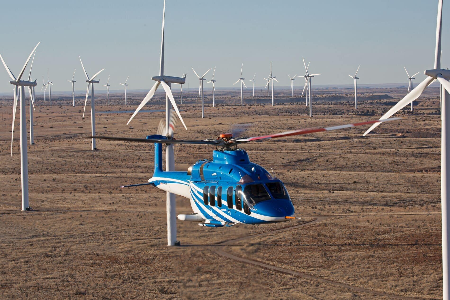Bell 525 volando sobre un campo eólico en el desierto