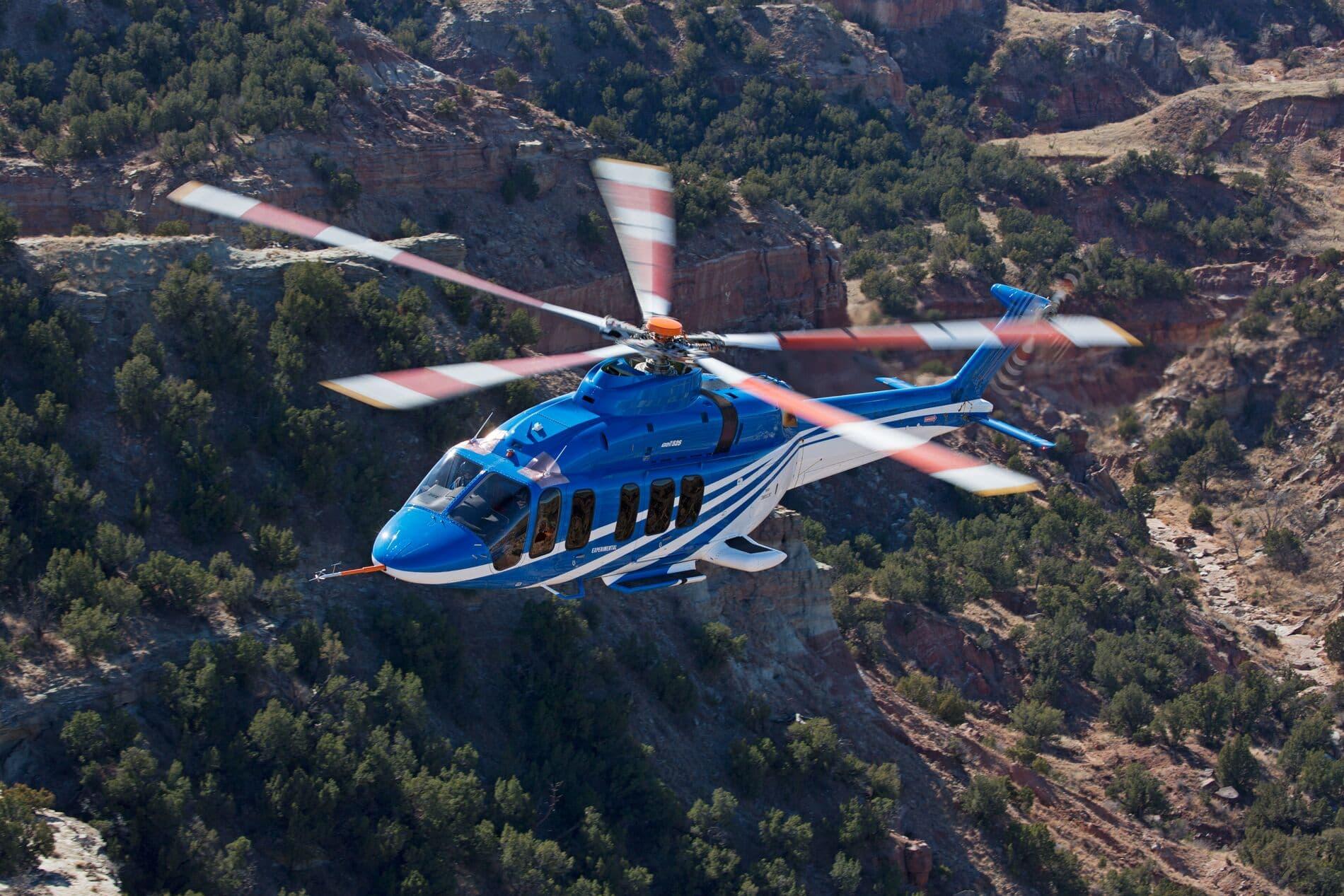 Bell 525 en vuelo sobre montañas verdes del desierto