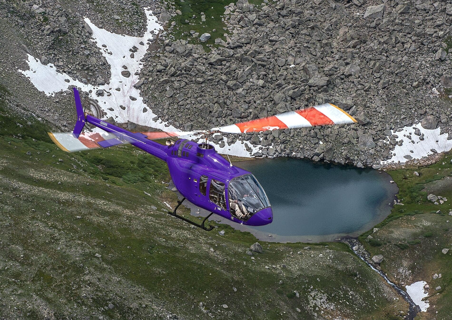 Un Bell 505 color púrpura sobrevolando las montañas.